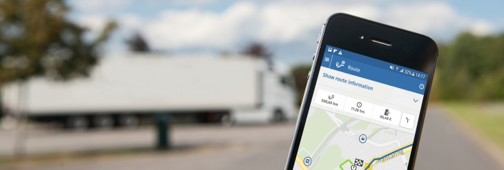 The screen of a smartphone shows the Toll Collect app. A truck is parked in the background.